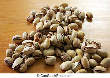 Pistachio nuts in a pile on wooden background