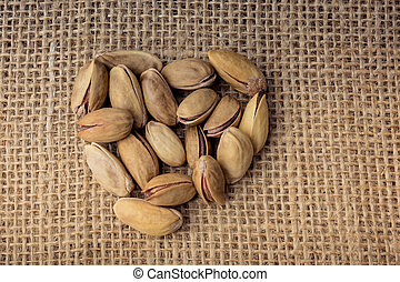 Pistachios form a heart shape on canvas