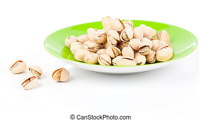 pistachios in a green plate, isolated on white background