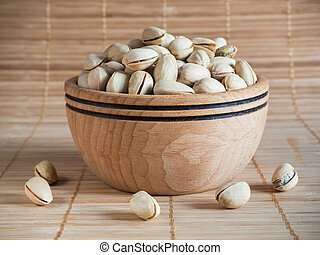 Pistachios in a wooden bowl. Close up.