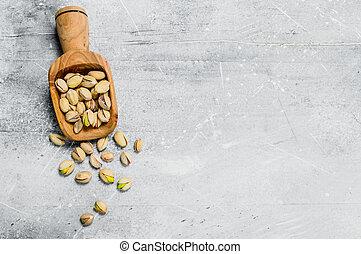 Pistachios in a wooden scoop.