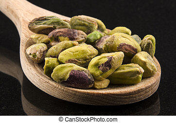 pistachios on a wooden spoon - pistachios on a kitchen spoon