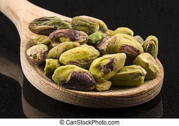 pistachios on a wooden spoon - pistachios on a kitchen spoon