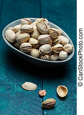Pistachios on petrol-colored wood in bowl