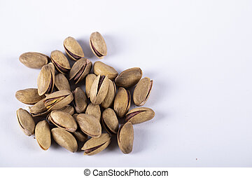 Pistachios on the left side of a white background