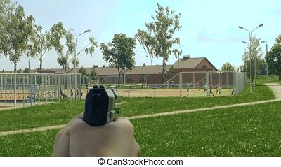 pistol in hands aims at kids on playground, children at...