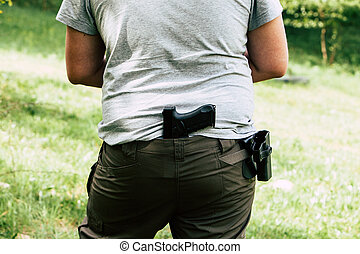 Pistol in the holster. The shooter trains. Is preparing to shoot at the target
