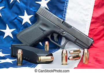 Pistol on flag - A handgun with a full magazine and...