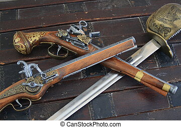 Pistols and swords - Pirates pistols and sword on a wooden...