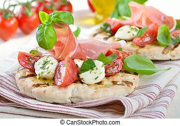Pita bread with delicious Italian ham, cherry tomatoes, mini-mozzarella and basil