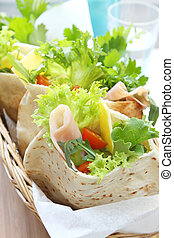 A basket of pita bread pockets filled with ham and salad. Healthy eating.