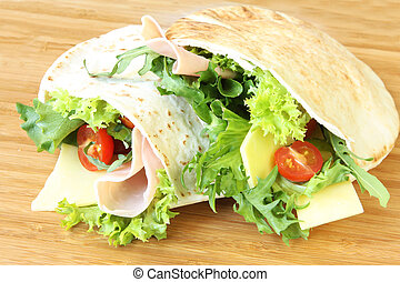 Pitta bread pockets filled with salad, ham and cheese.