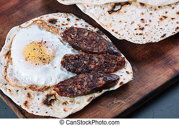 Pita with fried egg and pieces of salami on a wooden cutting board on grey background