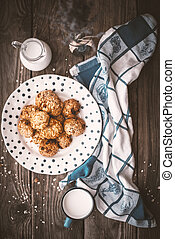 Pitcher, lavender, oatmeal cookies and a cup of milk on old boards