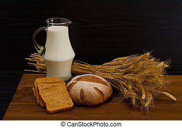 Pitcher of milk, round rye bread, a sheaf of wheat, bread slices on a wooden table