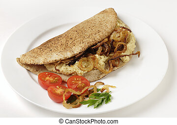 Pitta bread with hommos and onions - A pitta bread, or kubz,...