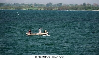Pixelated fishermen rowing in lake Malawi, slow-motion with text space