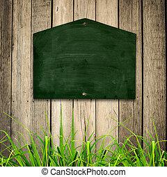 pizarra, con, hierba verde, en, de madera, fondo.
