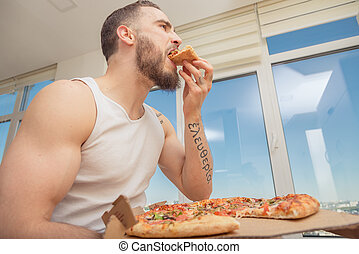 Pizza. A guy with a beard eats pizza