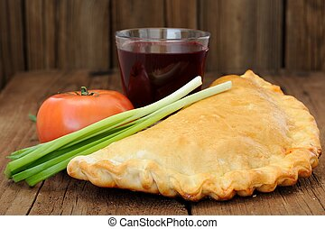 Pizza calzone with glass of red wine, fresh scallion and tomato