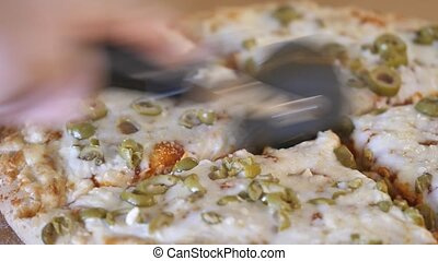 Pizza cutter slicing through fresh dough mozzarella and ...