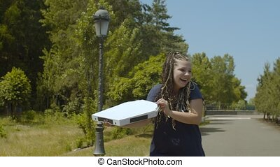 Pizza delivery woman on roller blades in park - Young female...