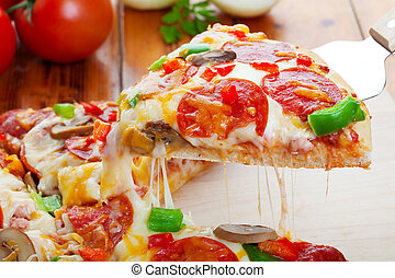 A slice of hot pizza deluxe with pepperoni, mushrooms, peppers, & lots of gooey mozzarella cheese, ready to be served.