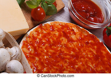 Pizza dough smeared tomato sauce. ingredeinty and on the...
