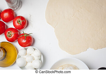 Pizza dough with ingredients served on a white table