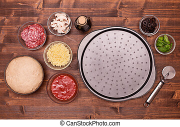 Pizza ingredients ready to be laid on the baking plate