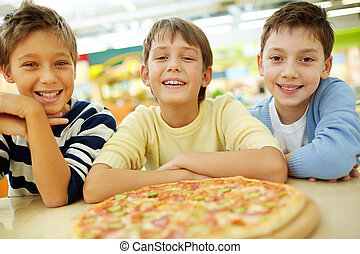 Pizza lovers - Three boys thrilled with pizza looking at...