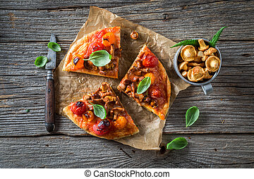 Pizza made of noble mushrooms and tomatoes on wooden table