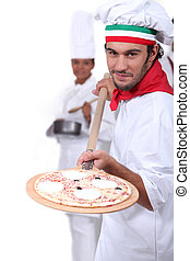 Pizza maker displaying his pizza