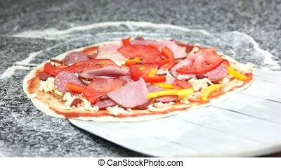 Pizza on a shovel. Thin crust, meat and vegetables.
