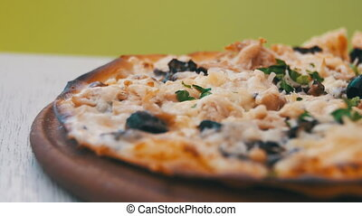 Pizza on a White Wooden Table in a Cafe. Dolly Shot....