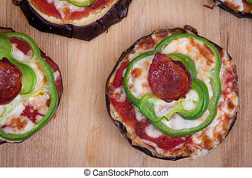 pizza on grilled eggplant slices on table