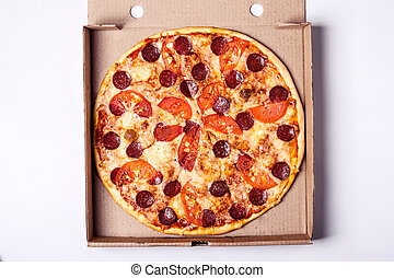 Pizza pereroni in packing box on gray background