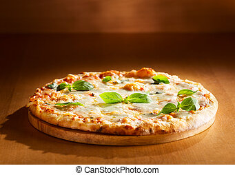 Pizza quattro fromaggi with basil on wooden background