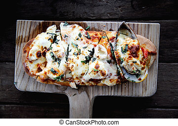 pizza seafood on wood background , italian food