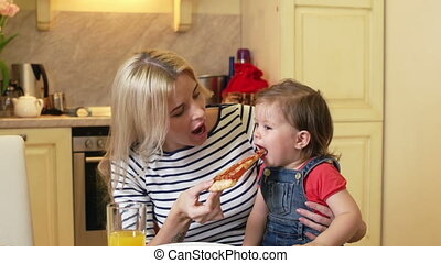 Pizza Slice - Mom giving a slice of pizza to her little...