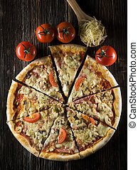 Sliced fresh pizza on wooden background close up