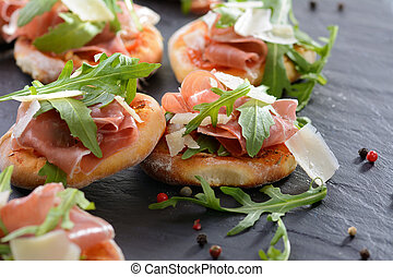Pizza snacks with parma ham, rucola leaves and parmesan...