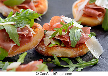 Pizza snacks with parma ham, rucola leaves and parmesan ...