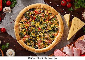 Pizza still life. Part of freshly baked pizza and its components arranged on wooden background.