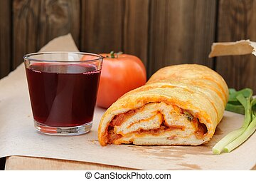 Pizza stromboli cut with glass of red wine, fresh scallion and tomato copyspace