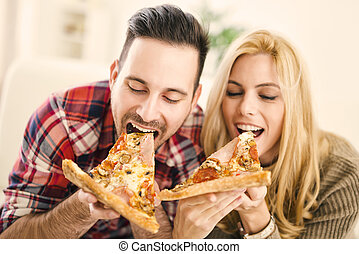 Pizza time - Portrait of an happy couple.They are laughing...