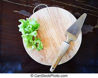 pizza turner and salad vegetable on wooden circle chopping block with copyspace in the middle