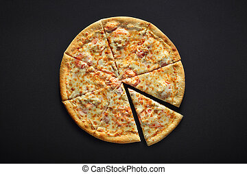 Pizza with cheese ham and tomato on a black stone background