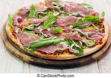 Pizza with dry cured ham on wood table