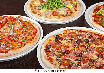 pizza with ham and mushrooms - different pizza at the table
